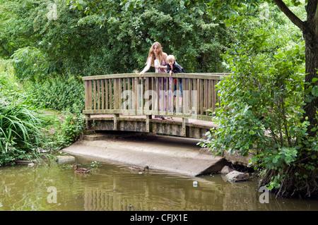 Caucasian woman with 8 year old Caucasian boy feeding mallard ducks at Barrs Court Moat Pond, near Longwell Green - Stock Photo