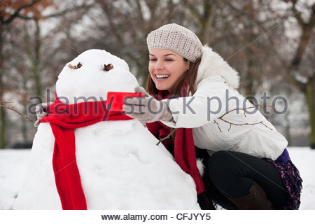 A young woman taking a photograph of a snowman - Stock Photo