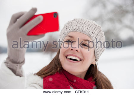 A young woman taking a photograph of herself in the snow - Stock Photo