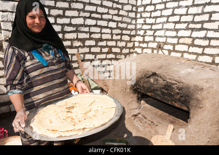 Woman with just made traditional Aich bread Minya Egypt - Stock Photo