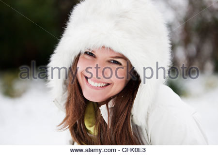 Portrait of a young woman wearing a fur coat, smiling - Stock Photo