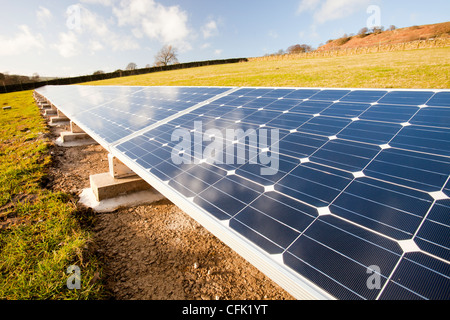 A farm house on the edge of Ilkley moor that has solar panels in the field behind the farmhouse to help power the - Stock Photo