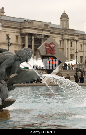 Trafalgar Square central London England United Kingdom the dolphin fountain with the Omega Olympic countdown clock - Stock Photo