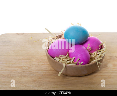 A small wooden bowl filled with colorful eggs and straw sitting on a table - Stock Photo