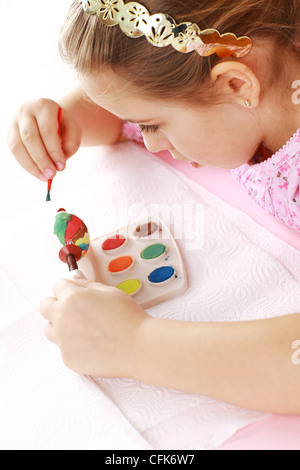 Cute little girl painting Easter eggs - Stock Photo