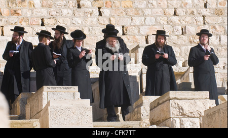Ultra Orthodox Jews praying in the cemetery on the Mount Olives in Jerusalem Israel - Stock Photo