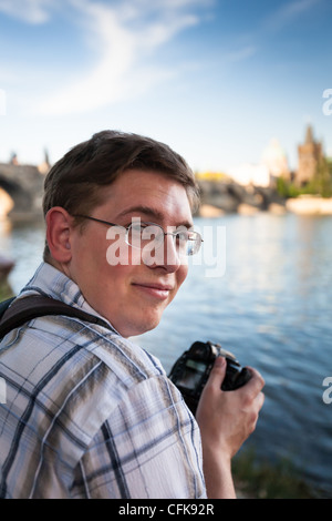 Young tourist taking pictures near the Charles Bridge in Prague, Czech Republic - Stock Photo