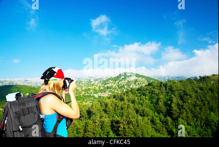 Tourist girl taking pictures of a high green mountains landscape, tourism travel vacation fun concept - Stock Photo