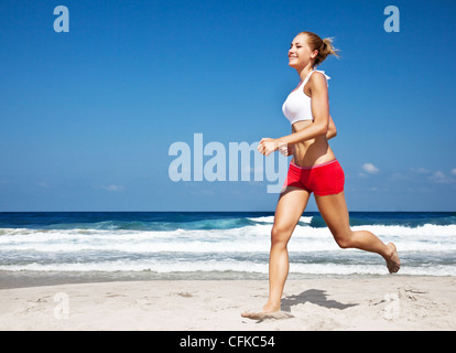 Healthy woman running on the beach, doing sport outdoor, freedom, vacation, heath care concept with copy space over - Stock Photo