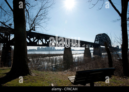 An empty bench faces the bridge over the Ohio river to Louisville, USA - Stock Photo
