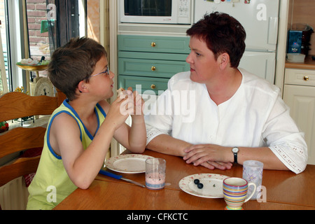 Mother and son sit and talk at breakfast table - Stock Photo