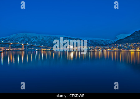 View from Tromso in Norway across the Norwegian sea looking towards Tromso Eismeerkathedrale in the middle of the - Stock Photo