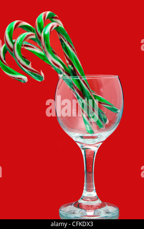 Festive still life of Christmas candy canes in a wine glass on a red background - Stock Photo