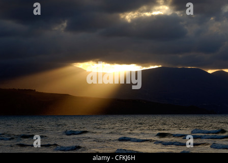 Castellammare del Golfo. Sicily. Italy. View of the inspirational and powerful sun rays pushing through the clouds - Stock Photo