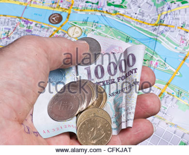 Mans hand holding Hungarian Forint money over map of Budapest - Stock Photo