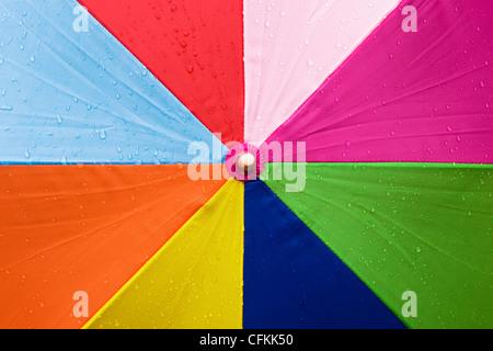Close up of a multicoloured umbrella in the rain. - Stock Photo