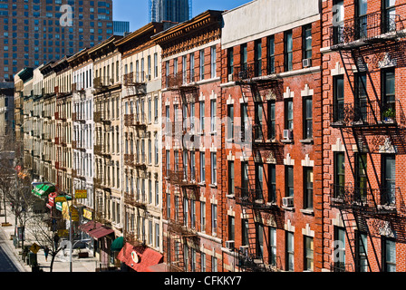Fire escapes on tenement apartment buildings in Harlem neighborhood, New York City. - Stock Photo