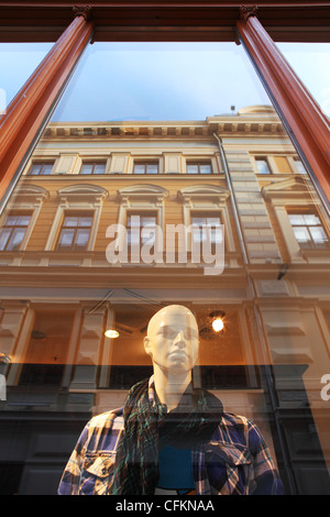 Vertical oriented image of mannequin stands behind the window with building reflection in Riga, Latvia. - Stock Photo
