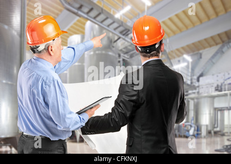 A team of construction workers with orange helmets at work place in a factory - Stock Photo