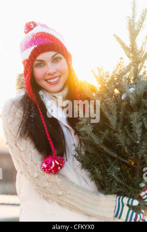 USA, New Jersey, Jersey City, Portrait of young woman carrying Christms tree - Stock Photo