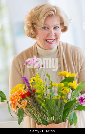 USA, New Jersey, Jersey City, Smiling senior woman arranging flowers - Stock Photo