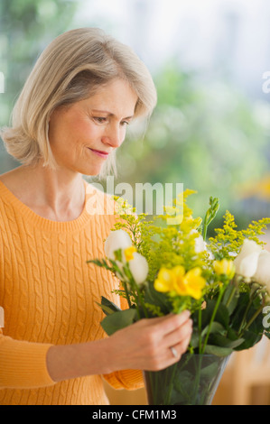 USA, New Jersey, Jersey City, Portrait of senior woman arranging bouquet in Mother's Day - Stock Photo