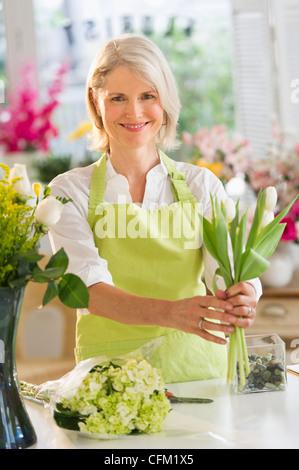 USA, New Jersey, Jersey City, Senior female florist arranging bouquet - Stock Photo