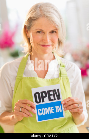 USA, New Jersey, Jersey City, Portrait of senior female florist showing open sign and smiling - Stock Photo