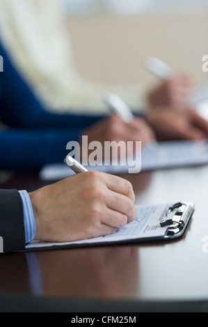 Jersey City, New Jersey, Close up of man's hands filling application form - Stock Photo