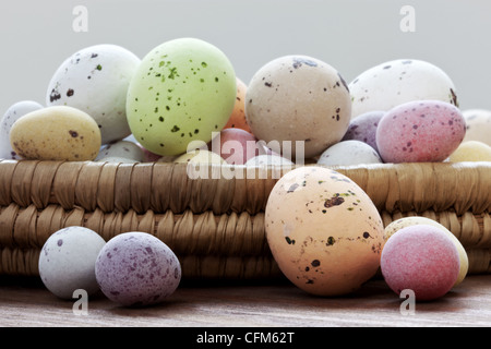 Still life photo of speckled candy covered chocolate easter eggs in a wicker basket on a rustic wooden table. - Stock Photo