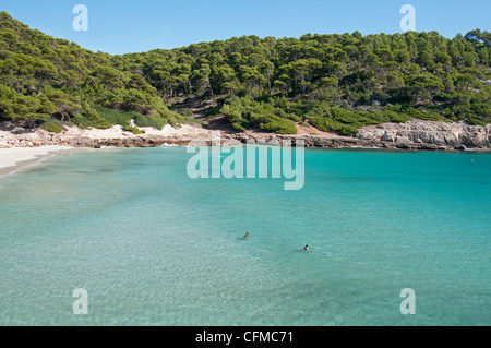 Swimmers in the shallows of the secluded beach of Trebaluger on the island of Menorca Spain - Stock Photo