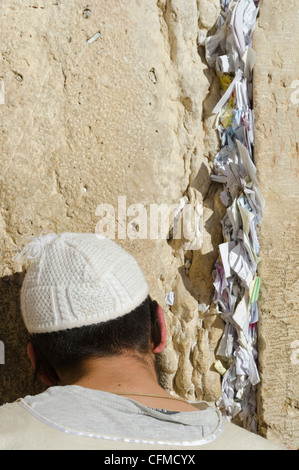 Orthodox Jew praying at Western Wall, with paper notes in crack, Old City, Jerusalem, Israel, Middle East - Stock Photo