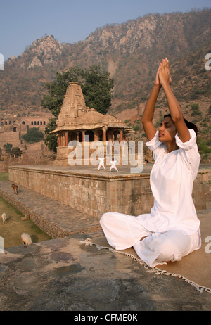 Women practising yoga in the abandoned town of Bhangarh, Alwar, Rajasthan, India, Asia - Stock Photo