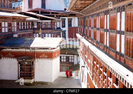 Two Buddhist monks chatting against the imposing backdrop of Trongsa Dzong, Trongsa, Bhutan, Asia - Stock Photo