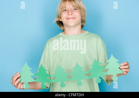 Studio shot portrait of teenage boy holding paper chain, waist up - Stock Photo