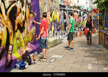 Horizontal view of Graffiti Alley Werregaran Straat in Ghent, with two artists spray painting their art onto the - Stock Photo