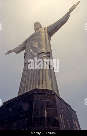 Christ the Redeemer statue of Jesus Christ rises above Rio de Janeiro Brazil atop Corcovado mountain - Stock Photo