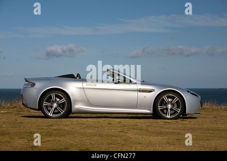 Aston Martin V8 Vantage Roadster convertible parked on a cliff top - Stock Photo