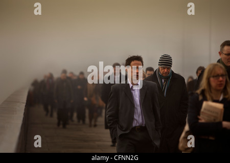Commuters crossing London Bridge on a smoggy morning - Stock Photo