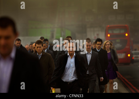 Commuters and busy traffic crossing London Bridge on a smoggy morning - Stock Photo