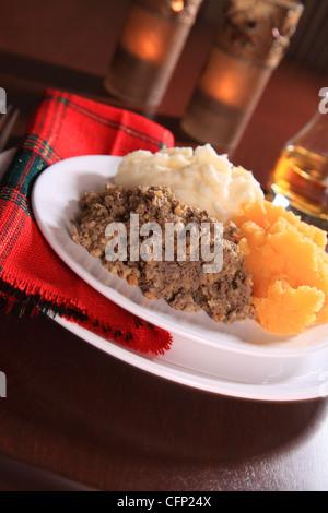 Scottish Haggis Serving For A Burns Night Dinner Against A Royal Stuart Tartan - Stock Photo
