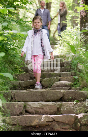 Girl walking down stone steps in woods, parents in background - Stock Photo