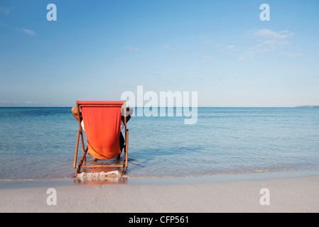 Man sitting in deckchair looking at ocean, rear view - Stock Photo