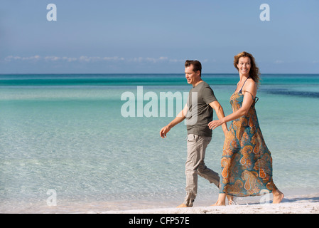 Couple walking leisurely on beach - Stock Photo