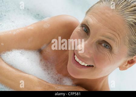 Mature woman enjoying bubble bath, tilt - Stock Photo