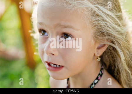 Littel girl looking up anxiously, portrait - Stock Photo
