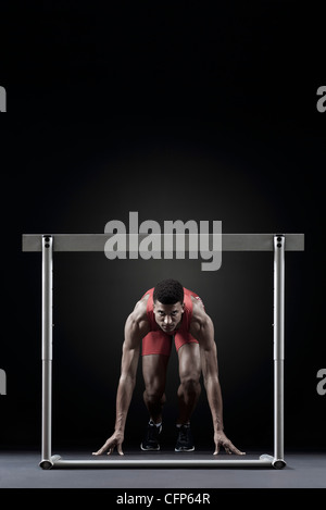 Male athlete at starting position in front of hurdle - Stock Photo