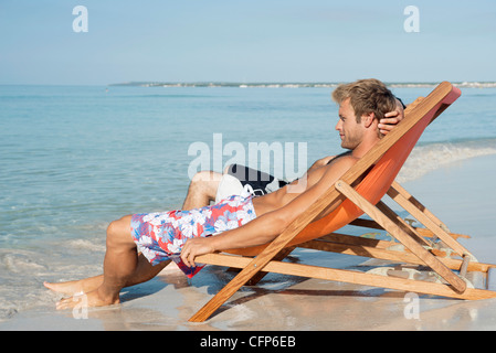 Two men sitting side by side on beach looking at ocean - Stock Photo