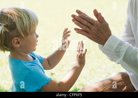 Little girl playing clapping game with grandmother, cropped - Stock Photo