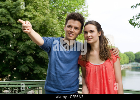 Young couple outdoors, young man pointing into distance, portrait - Stock Photo